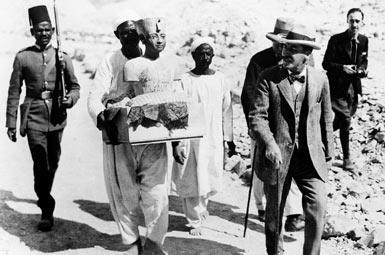 Говард Картер выходит из гробницы в сопровождении работников со статуей Тутанхамона